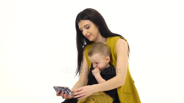 Mother holds her son on her lap and trains him. White background