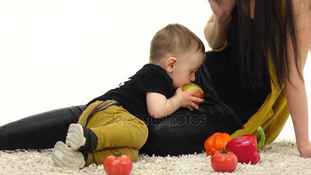 Ein kleines Kind isst neben seiner Mutter einen Apfel. weißer Hintergrund