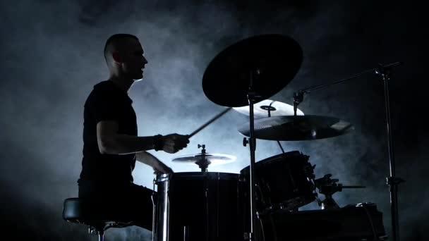 Energico musicista suona buona musica alla batteria. Sfondo nero e fumoso. Vista laterale. Sagoma. Slow motion
