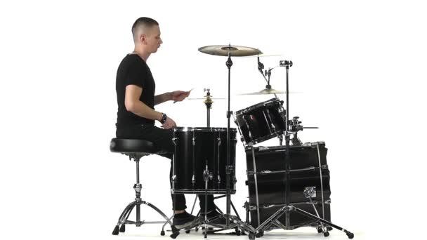 Mann spielt professionell Schlaginstrumente. weißer Hintergrund. Seitenansicht. Zeitlupe