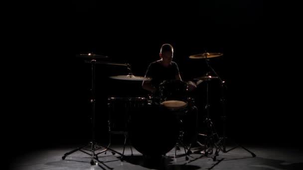 Profesionální hudebník hraje hudbu na bicí s pomocí hole. Černé pozadí. Silueta
