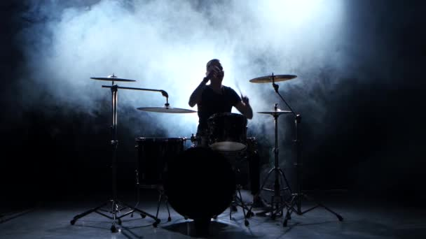 Energetic musician plays good music on drums. Black smoky background. Silhouette