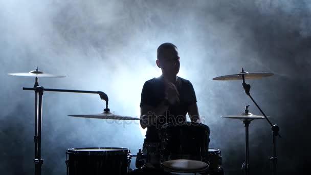 Profesionální hudebník hraje hudbu na bicí s pomocí hole. Zakouřený pozadí. Silueta