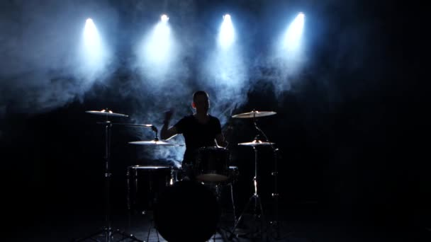 Energetic musician plays good music on drums. Black smoky background. Back light. Silhouette.