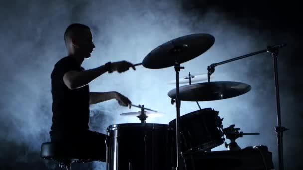 Energický hudebník hraje na bicí dobrou hudbu. Černé kouřové pozadí. Boční pohled. Silueta