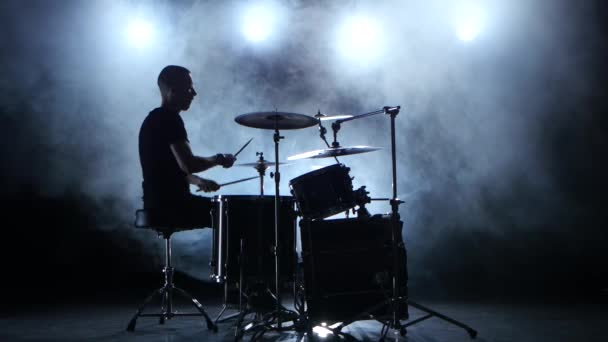 Hudebník hraje na bicí pomocí hole profesionálně dobrou hudbu. Zakouřený pozadí. Silueta