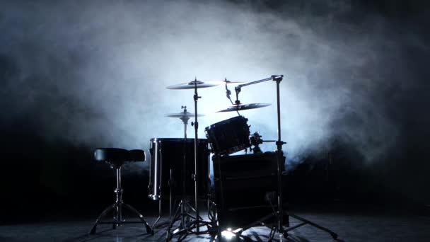 Set of drums, cymbals and other percussion instruments. Black smoky background. Back light.
