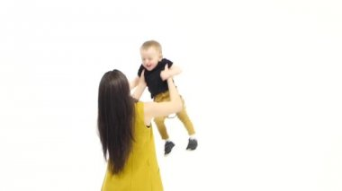 Girl circles around her son, he laughs. White background. Slow motion