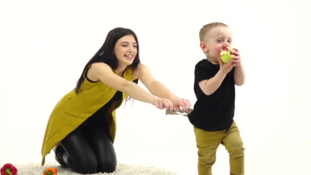 Girl sits on the floor, next to the vegetables lie, she tries to hold the baby. White background. Slow motion