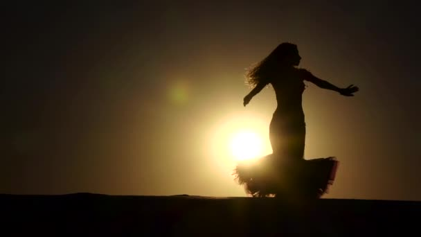 Girl dancer dances gracefully against the background of a hot sunset. Silhouette. Slow motion