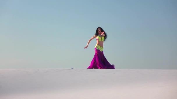 Anmutige Tänzerin gegen den himmelblauen Bauchtanz in brillantem Outfit. Zeitlupe