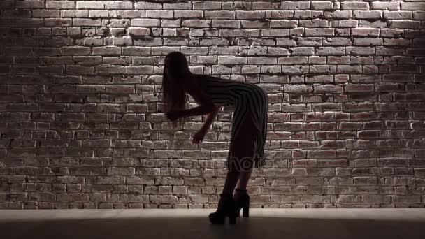 Nő magas, magas sarkú tánc twerk ellen a téglafal. Sziluettjét. Lassú mozgás