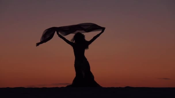 Girl gracefully dances with a veil of hands against a sunset. Silhouette