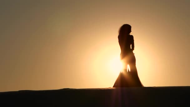 Dancer dances gracefully against the background of a hot sunset. Silhouette