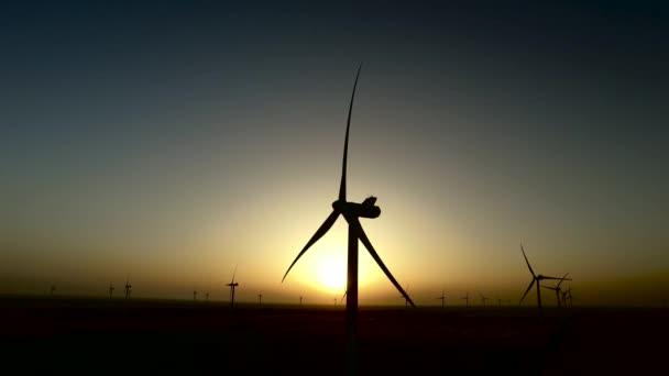 Munka a szélturbinák, a búza mezők alatt a színes nyári naplementében. Sziluettjét. Légi felmérés