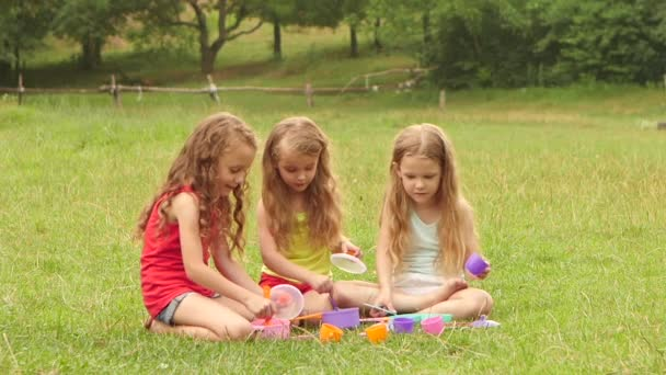 Three girls playing with toys on nature. Slow motion