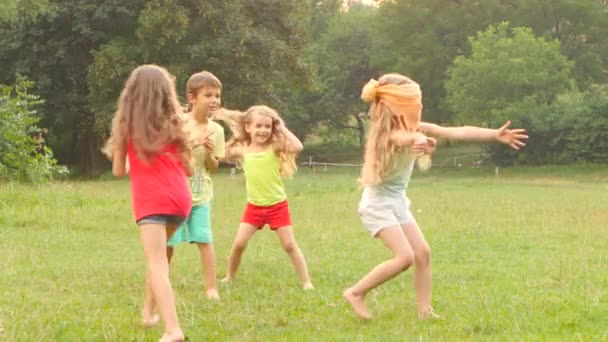 Cheerful children playing tag on the grass on a summer day