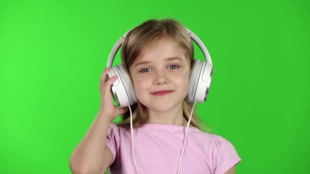 Baby listens to music through the headphones. Green screen. Slow motion