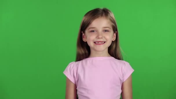 Child genuinely smile at the camera. Green screen. Slow motion
