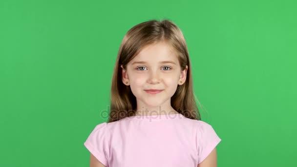 Kind lächelt aufrichtig in die Kamera. Green Screen