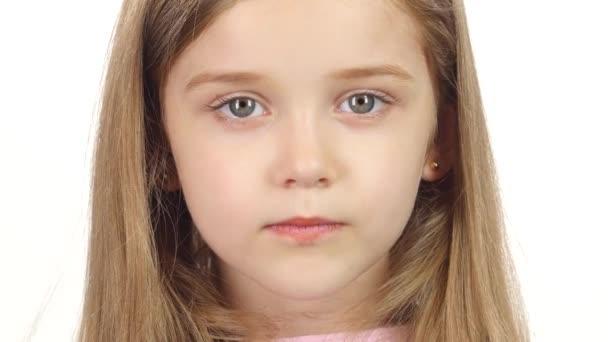 Kind lächelt aufrichtig in die Kamera. weißer Hintergrund. Nahaufnahme