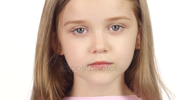Kislány valóban mosolyogni a kamera. Fehér háttér. Közelről