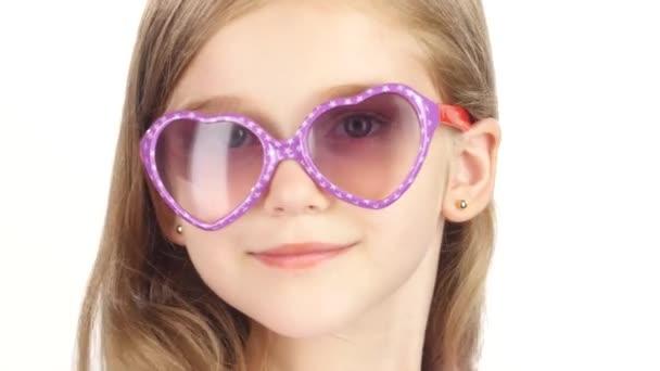 Dítě představuje pro videokamery s brýlemi. Bílé pozadí. Detailní záběr