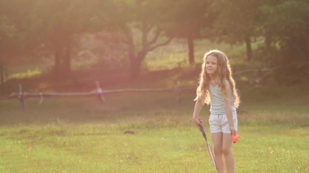 lockiges hübsches Mädchen, das im Park Badminton spielt. Zeitlupe