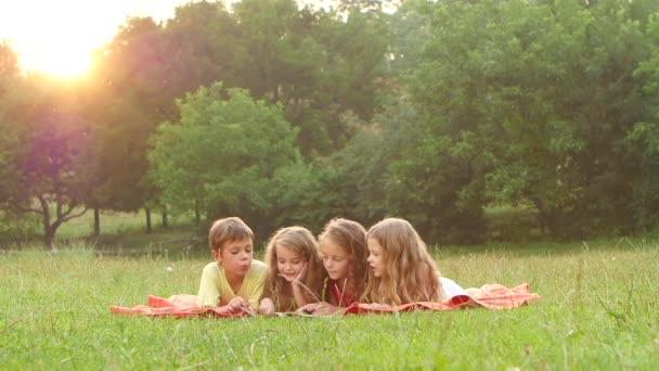 Šťastné děti zalistovat knihou v zahradě na trávníku, v létě denně. Zpomalený pohyb