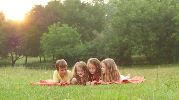 Adorable children reading a book on a lawn together summer nice afternoon. Slow motion