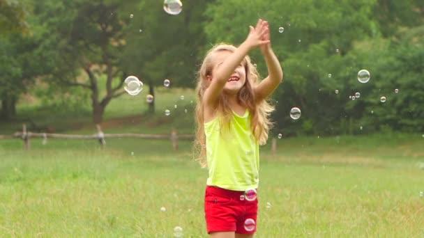 Usmívající se dívka bavit hrát catch mýdlové bubliny v letním parku. Zpomalený pohyb