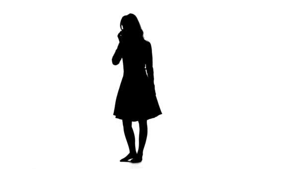 Lány tartja a telefont, a kezét és mosolyogva. Fehér háttér. Sziluettjét