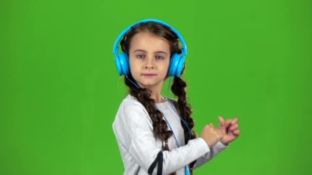 Baby im Kopfhörer hört Musik. Green Screen. Zeitlupe