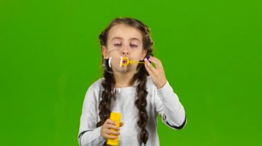 Child with soap bubbles. Green screen