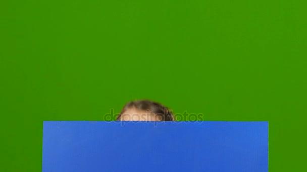 Dítě vypadá zezadu blue board a ukazuje palec. Zelená obrazovka