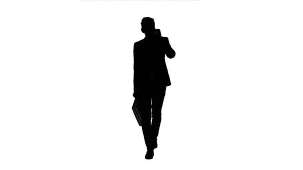 Az ember megy dolgozni, és beszél a telefonon. Fehér háttér. Sziluettjét
