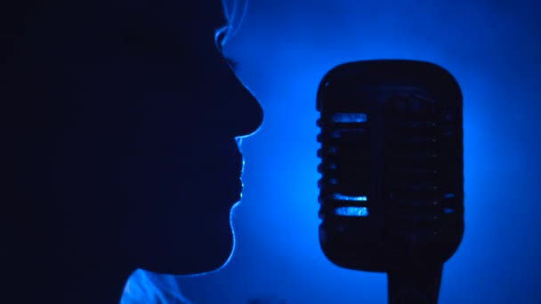 Photo Singer sings in a retro microphone. Smoke background. Silhouette. Side view. Close up