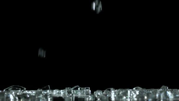 Krystaly a diamanty padat a dopadl na podlahu. Černé pozadí. Zpomalený pohyb