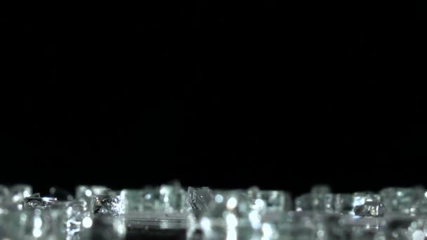 Střepy skla spadnout na zem. Černé pozadí. Zpomalený pohyb
