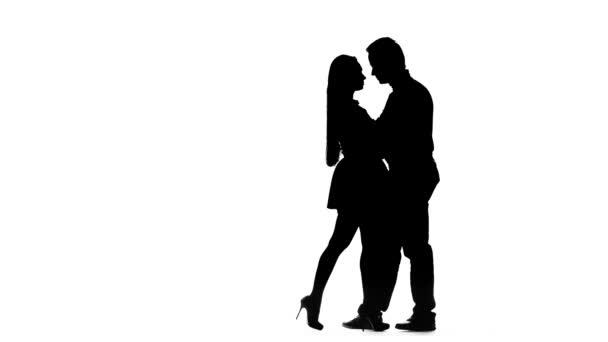 Liebespaar tanzt im Studio lateinamerikanische Tänze. Silhouette. weißer Hintergrund