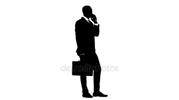 Muž drží aktovku a hovoří do telefonu. Bílé pozadí. Silueta