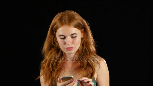 Mädchen schaut auf das Foto auf ihr Handy. Schwarzem Hintergrund