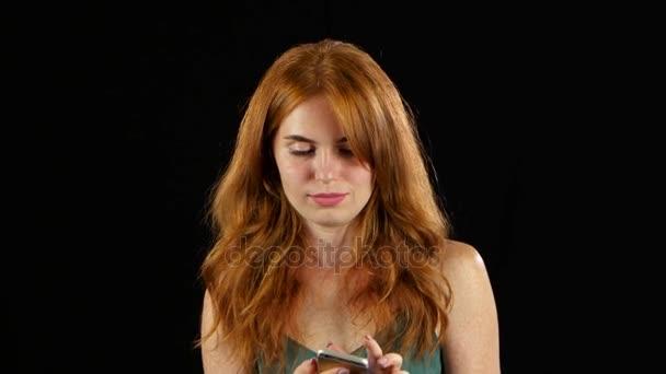 rothaarige Mädchen am Telefon. schwarzer Hintergrund