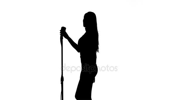 Singer performs songs in a retro microphone  Silhouette  White background