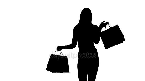 Žena balíčky v rukou pózuje pro kamery. Silueta. Bílé pozadí. Zpomalený pohyb