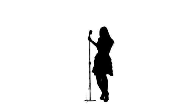 Mädchen singt in einem Retro-Mikrofon. Silhouette. weißer Hintergrund. Zeitlupe