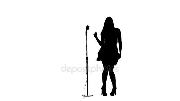 Frauen singen Lieder und tanzen in der Nähe eines Retro-Mikrofons. Silhouette. weißer Hintergrund. Zeitlupe