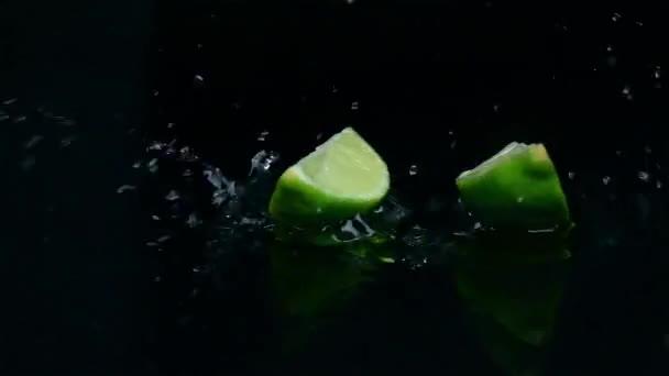 Zwei Stück Kalk fallen ins Wasser. schwarzer Hintergrund. Zeitlupe