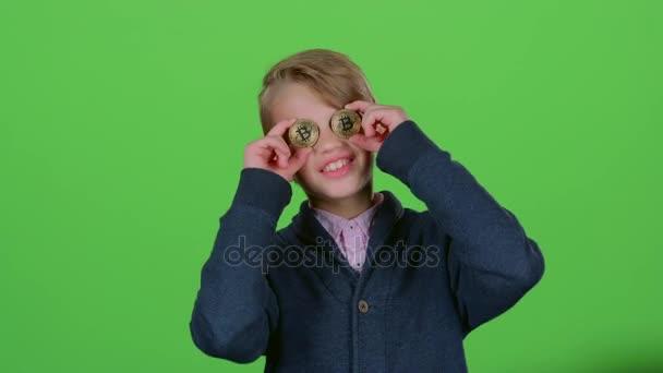Teen, usmívá se dvěma bitcoiny na zelené obrazovce