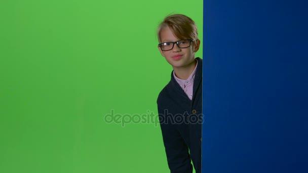 Boldog gyermek fiú szemüveg kukucskál ki a falról, egy zöld képernyő